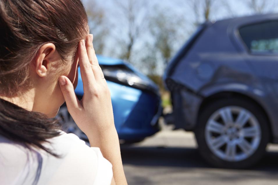 Kvinne som sitter foran to biler som har kollidert