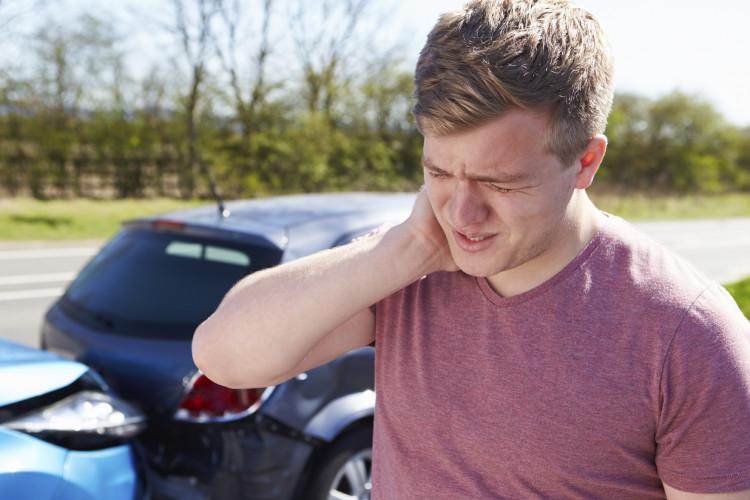 Mann som står foran en bil og holder seg i nakken