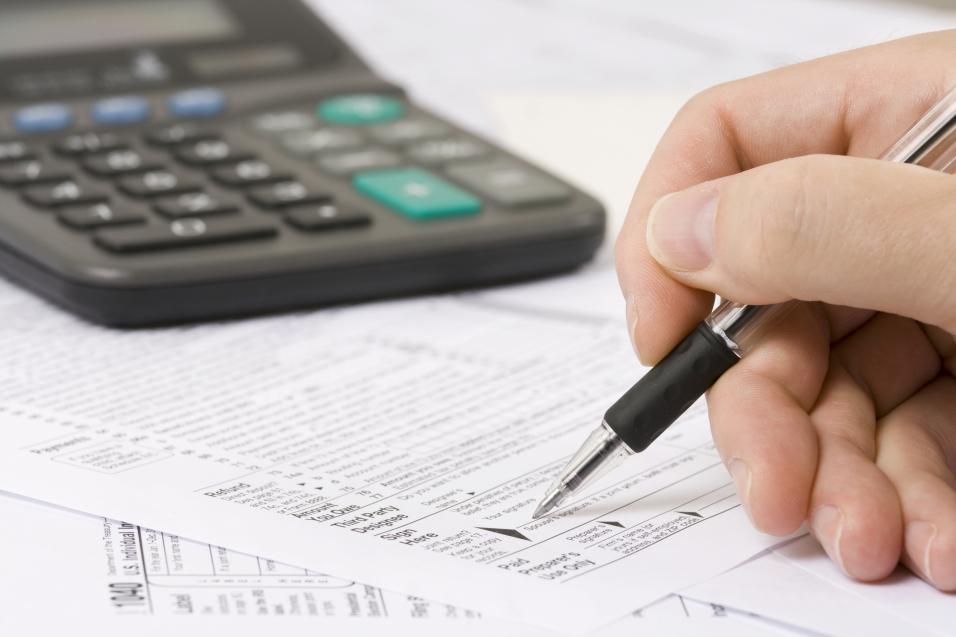Noen som skriver på et ark og har en kalkulator