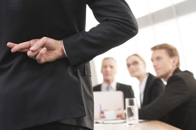 Bilde av en mann som krysser fingrene bak ryggen, mens menn i dress sitter foran ham.