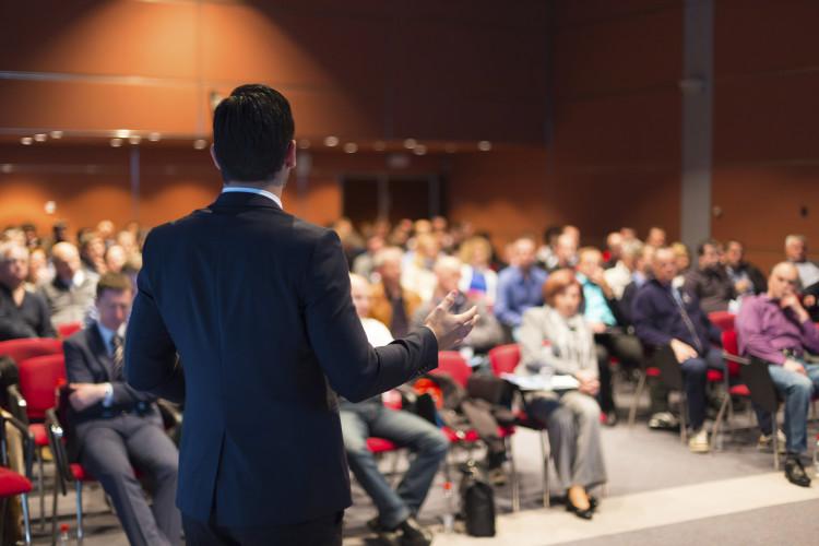 Mann som snakker foran en forsamling
