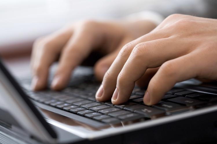 nærbilde av noen som skriver på en laptop