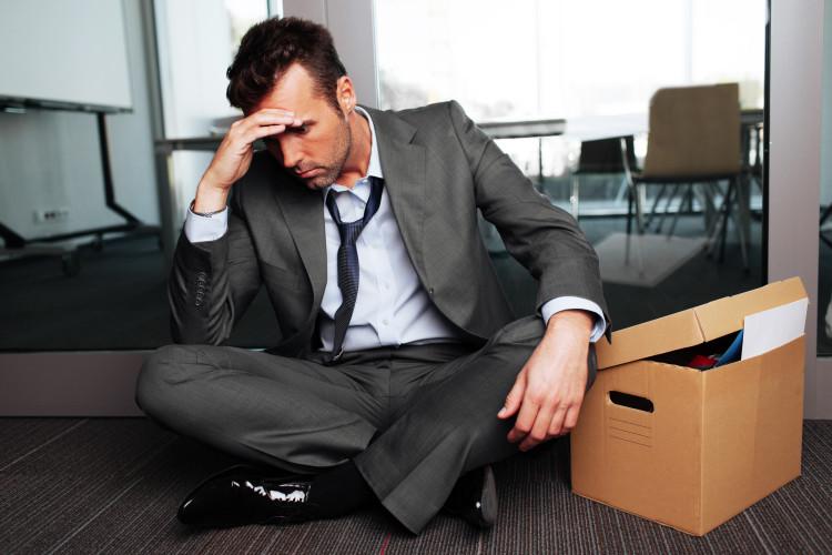 Mann som sitter utenfor kontoret sitt med en eske