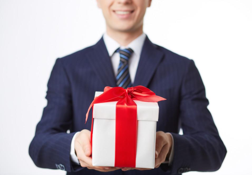 Mann i dress som holder frem en gave