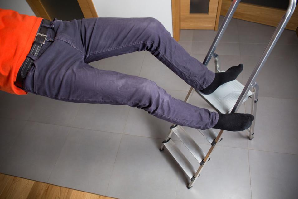 Mann som faller ned fra stige