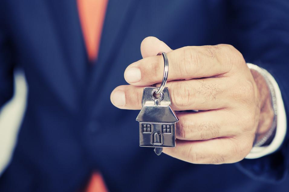 Mann som holder et nøkkelknippe formet som et hus