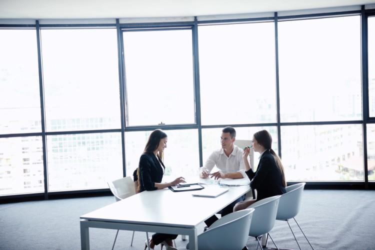 Mennesker i forretningsklær som sitter rundt et bord og ser på dokumenter