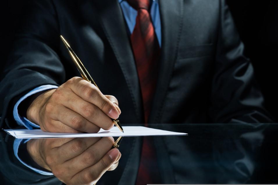 Mann i dress som skriver på et dokument
