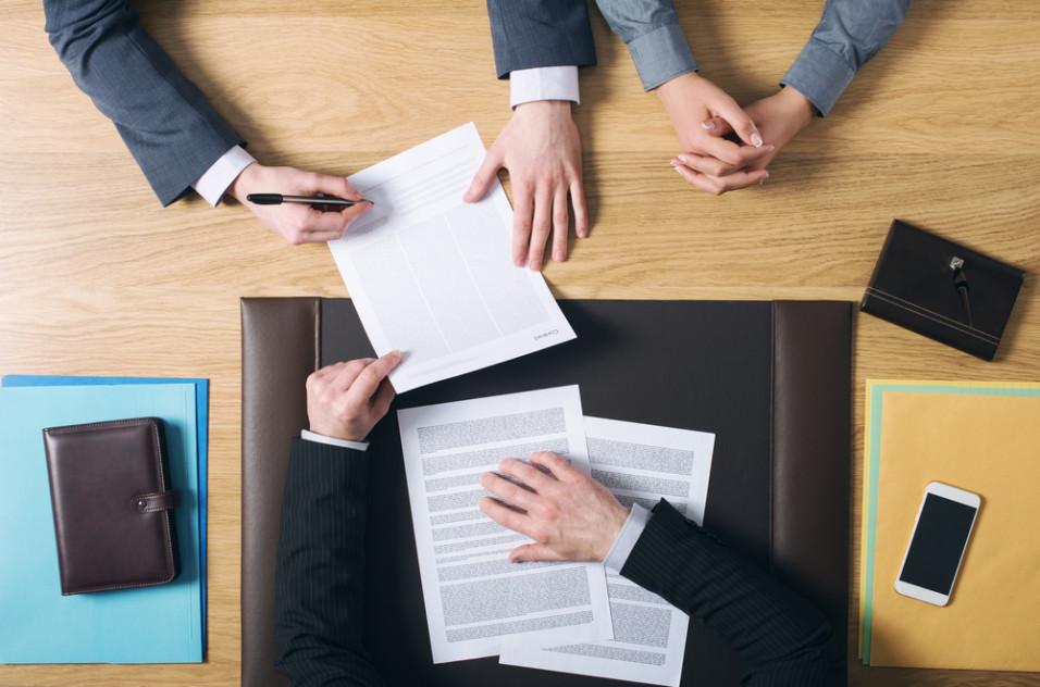 Tre personer som signerer og ser over papirer