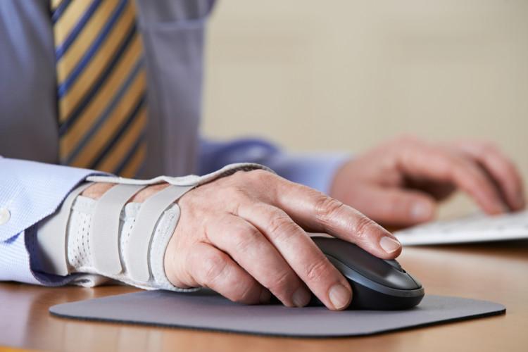 Mann med forstuet håndledd som jobber på pc