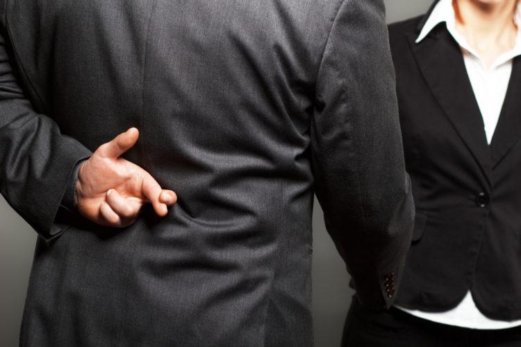 Mann som tar en kvikke i hånden mens han krysser fingrene bak ryggen