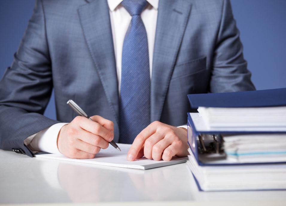 Mann som noterer med dokumenter på pulten
