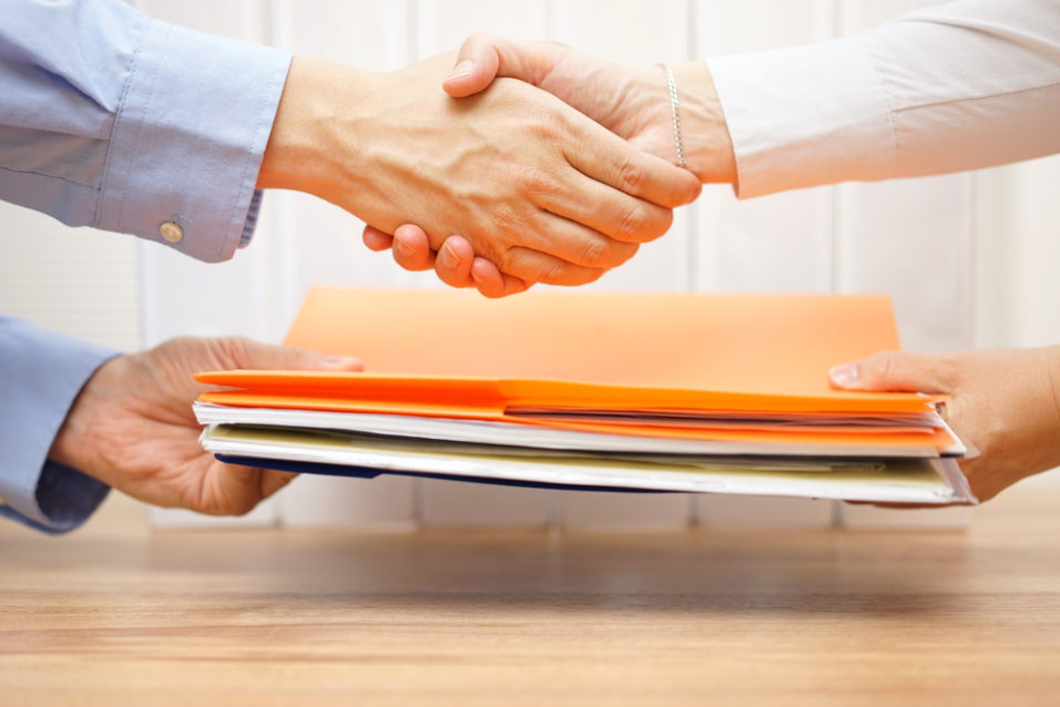 To personer som tar hverandre i hendene og utveksler dokumenter