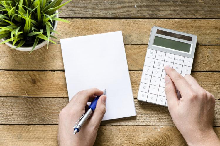 Person som skriver som ser på kalkulator
