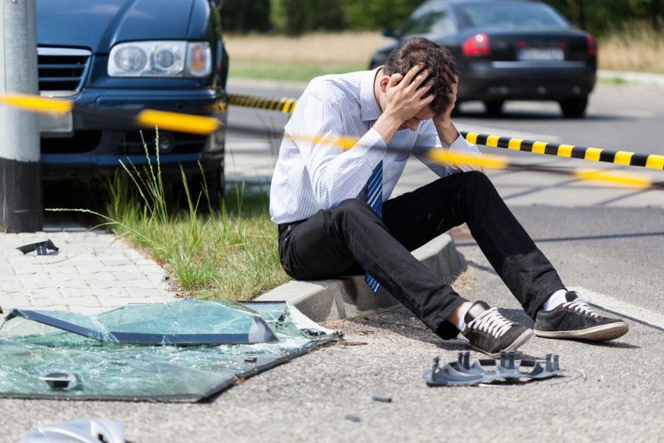 Mann som sitter ved siden av bilvrak