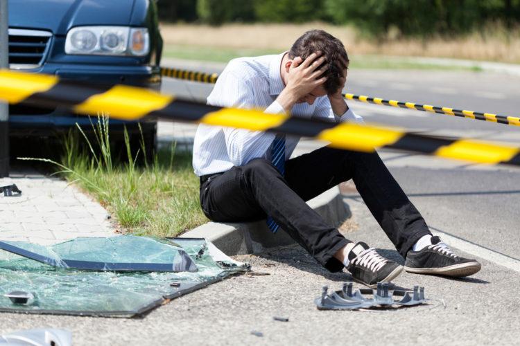 Man som sitter ved siden av et bilvrak