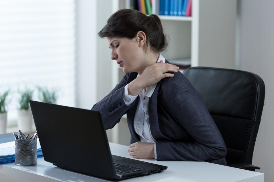 Kvinne som har vondt i skulderen