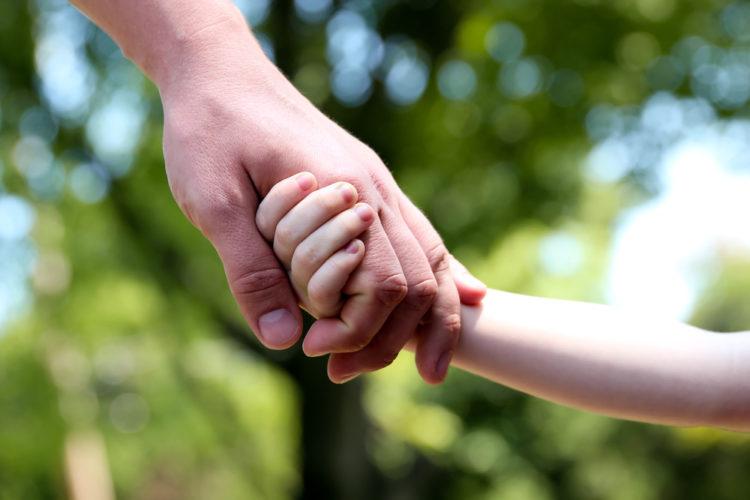 Et barn som holder en voksen i hånden