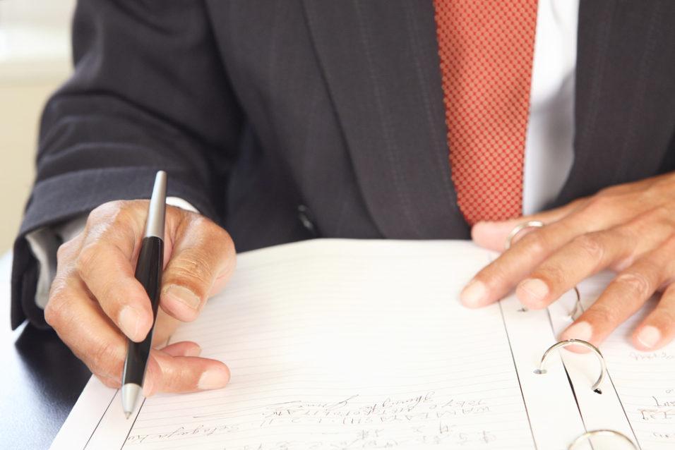 Mann som skriver på et dokument