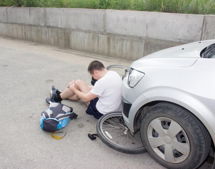 Mann på sykkel som er påkjørt av en bil